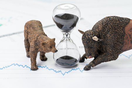 Time counting down to choose between investment bear and bull stock market concept, hourglass or sandglass on chart and graph, price list report paper surround by bear and bull figure. Banque d'images