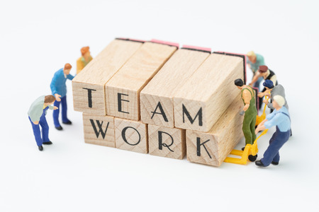 Teamwork concept idea, miniature people figurine work as team helping each other to build or develop wooden stamp combine the word Team work, challenge for business success. Stock Photo