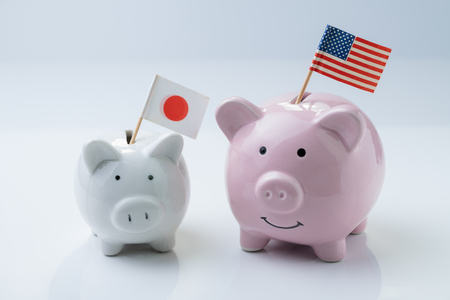 America and Japan friendship, talk, negotiation, economic and diplomacy concept, pink piggy bank with USA national flag with small white one with Japan flag on white background.