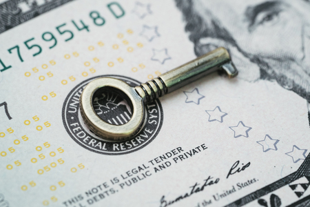 Key for world and United States economy, FED consider interest rate hike, important bronze mini key on US Federal Reserve emblem on dollars banknote. Stock Photo