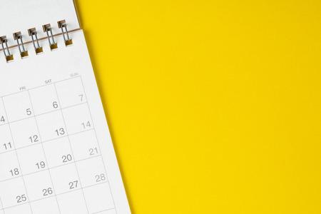 Calendario limpio blanco sobre fondo amarillo sólido con espacio de copia, calendario de reuniones de negocios, planificación de viajes o hito del proyecto y concepto de recordatorio. Foto de archivo