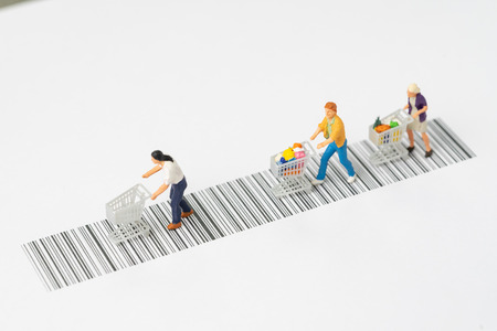 Miniature people figurine with grocery in the shopping cart rally on the bar code using as ecommerce, consumer or buy and sale in new technology channel concept. Stock Photo - 105819591