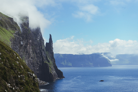 Beautiful view of Trollkonufingur (Witchs Finger) Fjord appear from clouds in blue sky next to North Atlantic ocean, hiking from Sandavagur village on Vagar island of the Faroe Islands. Stock Photo