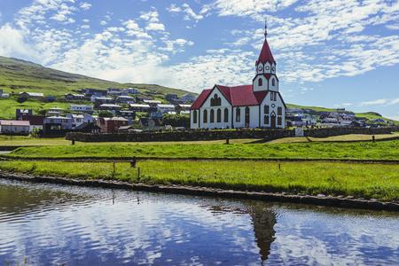Impresionante vista de la iglesia blanca con techo rojo bajo el hermoso sol en el cielo de nubes y el reflejo en el estanque frente a la iglesia junto al océano, la ciudad de Sandavagur en la isla de Vagar, Islas Feroe.