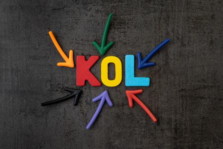 Abréviation KOL de Key Opinion Leader, concept d'influence, flèches colorées pointant vers le mot KOL au centre du mur de ciment noir, nouveau marketing des médias sociaux dans le monde numérique. Banque d'images