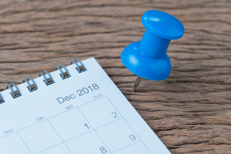 December 2018, year end review, date planning, appointment, deadline or holiday concept, big blue pushpin or thumbtack pin on wooden table next to white clean calendar on month of December.