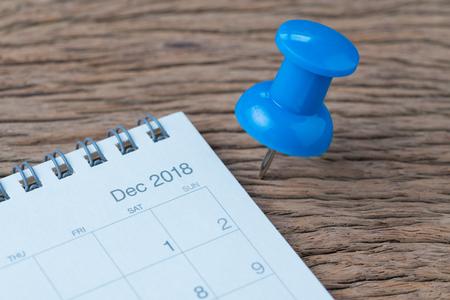 Dicembre 2018, revisione di fine anno, pianificazione della data, appuntamento, scadenza o concetto di vacanza, grande puntina da disegno blu o puntina da disegno sul tavolo di legno accanto al calendario pulito bianco nel mese di dicembre.
