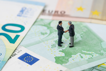 Europe, Brexit or Britain economy meeting or negotiation concept, miniature people businessman politician government handshaking on European map on Euro banknote, making a financial or economic deal.