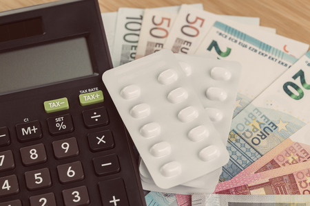 Health care, medical or pharmacy cost concept, white package of pills on pile of Euro banknotes money with calculator, patient have to pay for their better life.