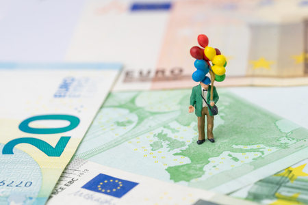 Europe, Brexit financial or economy concept, miniature people happy old man politician holding balloons on European map on Euro banknote. Stock Photo