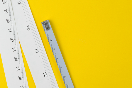 White measuring tapes with centimetre and inches on vivid yellow background with copy space, length, long or maker concept. Stock Photo