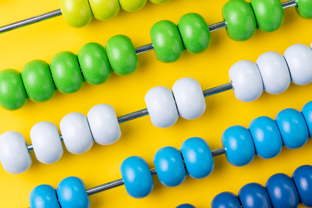 Colorful wooden abacus beads on yellow background, business financial or accounting profit and loss concept, or use in education school arithmetic symbol.