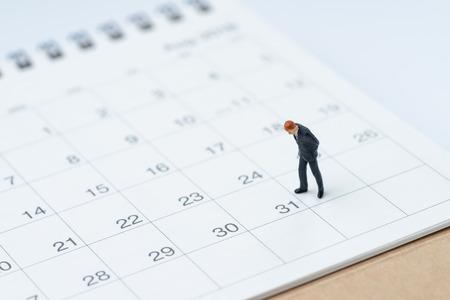 Fine del mese per il concetto di uomo di stipendio, ragazzo in miniatura uomo d'affari ufficio in piedi e guardando la data numero 31, in attesa di ottenere soldi e giorno di paga.