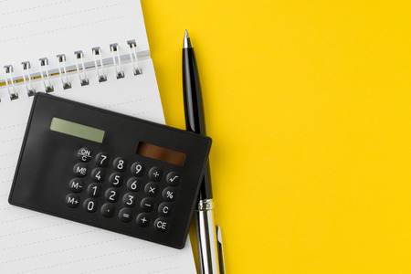 Flat lay or top view of black pen with calculator and white paper notepad on vivid yellow background table with blank copy space, math, cost, tax or investment calculation.