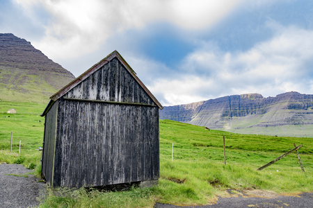 Beautiful view of black faded wooden barn with green grass of sheeps farm and high mountain cliff in the background with cloudy weather sky in Faroe Islands rural. 免版税图像