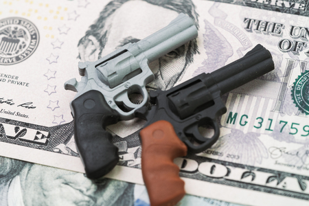American gun industry, gun control policy in united state of america concept, miniature toy guns on US dallar banknote.