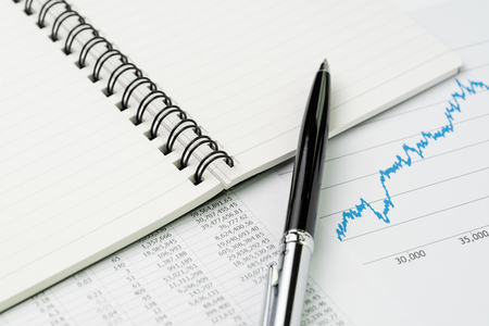 Financial performance report, market price list, stock, bond or equity analysis for investment concept, pen on notepad with graph and chart reports on table.