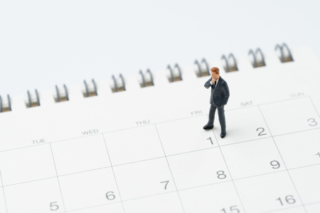 Inizio o inizio del mese per il concetto di uomo salariato, uomo d'affari in miniatura in ufficio in piedi a 1 data sul calendario, pronto per iniziare il nuovo mese lavorativo.