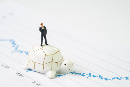 Invest with slow but steady for long term success metaphor, miniature people businessman riding turtle or tortoise walking on rising growth stock market value graph, value investment concept. Stock Photo