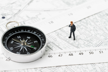Map of property or real estate location, direction, navigation and distance concept, miniature businessman standing with compass and measuring tape on transportation and building map with street. Reklamní fotografie