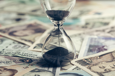 Time running or long term investment concept with sand glass or hour glass on many countries international banknotes, US Dollar, Thai Baht, Yuan, japan yen in vintage tone. 스톡 콘텐츠