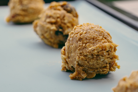 Closed up of cookie dough on baking sheet, brown hazelnuts, raisin and oatmeal put in scoop before put in the oven. 免版税图像