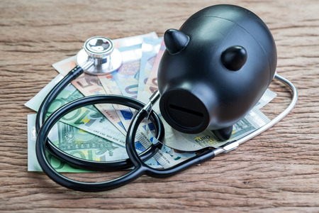 Finance health check on EU European union economic concept, black saving piggy bank with stethoscope on pile of Euro banknotes on wooden table, debt and financial crisis on Europe countries.