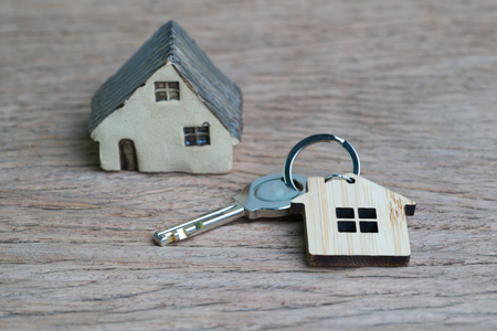 Saving money for first house or home mortgage loan concept, key with wooden house key chain on wooden table with copy space, real estate or property investment.
