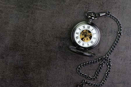 Vintage retro pocket watch on dark black chalkboard background with copy space using as time passing or long term condition concept.