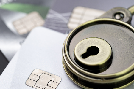Credit card online payment or shopping website data security concept, key lock pad on pile of credit cards, e-commerce safety encode to transmit data.