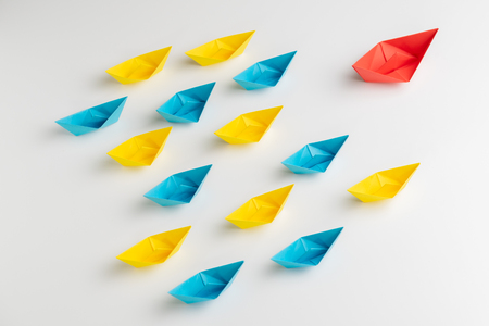 Influencer, KOL, key opinion leader or leadership concept, big red origami paper ship leads in front of others small yellow and blue fleet. Banco de Imagens