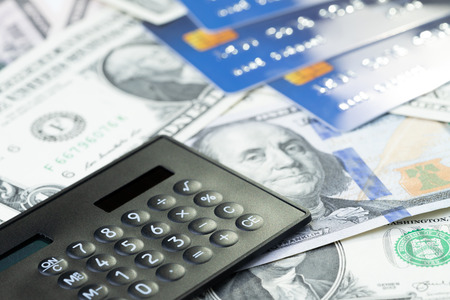 Credit card debt, financial problem or loan payment concept, calculator on US Dollar bills money and credit cards can use as cost, expense or spending plan background.