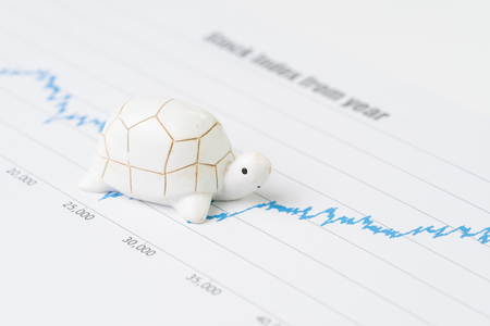 Sustainable with long term investment concept, miniature decorate turtle or tortoise slow walking on rising growth stock market value graph, value investment concept.
