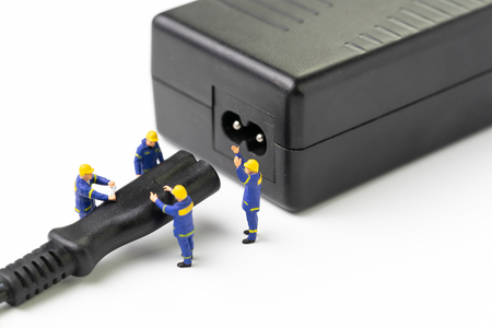 Sustainable energy, power consumption or electricity innovation concept, miniature people worker, technician help connect or power on AC electric on white background.