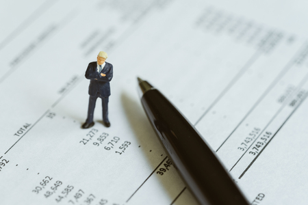 Accounting, investment, financial report analysis or expense and budget concept, miniature people figurine success businessman standing on financial profit and loss printed paper.