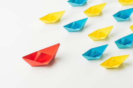 Key opinion leader, micro influencer or leadership concept, big red origami paper ship leads in front of others small yellow and blue fleet. Stock Photo