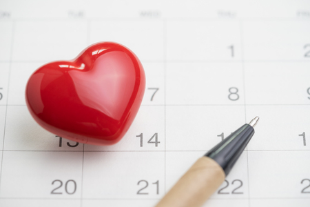 Love symbol or romance of valentine's day concept with shiny red lovely heart shape with pen on 14 Feb white clean calendar. Banque d'images