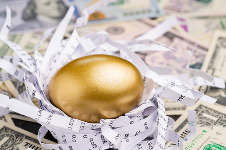 Shiny golden egg in paper nest with financial numbers on pile of US dollar banknote money metaphor of finding the good stock with high dividend or success investment in stock market concept.