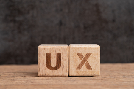UX User Experience design in product and service concept, cube wooden block building acronym UX on table with blackboard with copy space, user centric method. Stock Photo