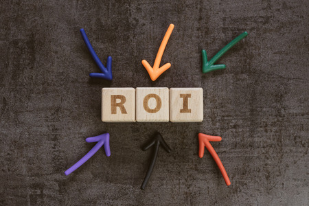 Return on Investment, ROI, performance measure of business or investment efficiency, target and goal, colorful arrows pointing to cube wooden block building the word ROI on chalkboard. Stock Photo