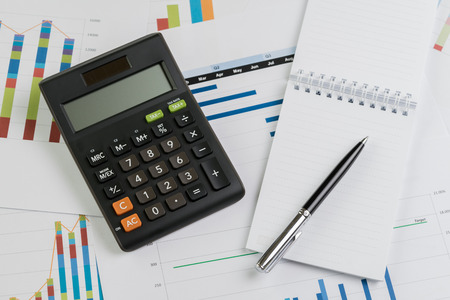 Finance profit and loss or business quarterly performance review concept, calculator, pen with paper note on bar graph and chart report document on office desk. Stock Photo