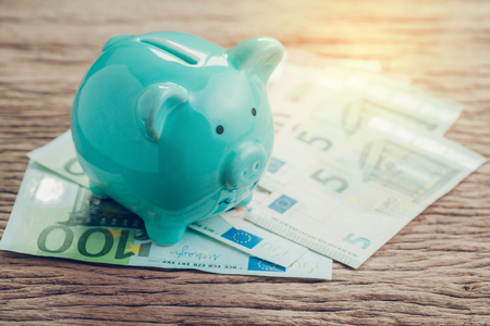 Money savings financial account, Europe economics concept, blue piggy bank on pile of Euro banknotes on wooden table, future growth of compound interest in saving or investing idea.
