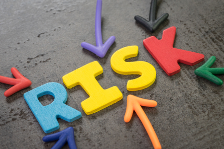 Colorful arrows pointing to the word RISK at the center of black chalkboard wall, business or investment risk, result in uncertainty, unpredictable situation concept, assessment of volatility.