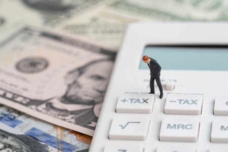 Tax calculation or tax refund for individual or company concept, miniature businessman leader standing and thinking with tax plus button on calculator and pile of US America Dollar banknotes money. Stock Photo