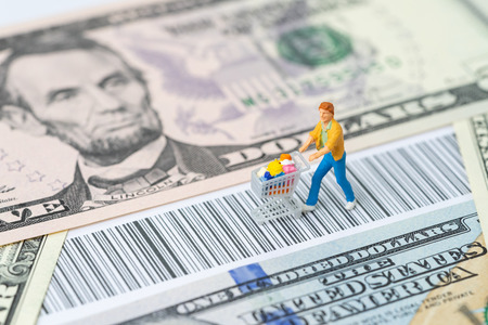 Miniature people figurine with grocery in the shopping cart trolley walking on the bar code with us dollar banknotes money using as e-commerce, consumer or buy and sale in new digital channel concept.