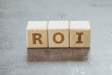 Return on Investment, ROI, performance measure of business or investment efficiency, target and goal, cube wooden block building the word ROI on chalkboard.