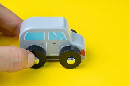 Adult hand holding cute wooden small toy car parking on vivid yellow background, car leasing, rental or insurance or automobile market concept. Stock Photo
