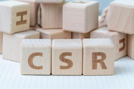 CSR, Corporate Social Responsibility concept, wooden cube block with letters forming acronym CSR on white gridline notebook, activity that company help people and community.