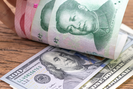 China and USA finance trade war talk or tariff discussion metaphor, US dollar banknotes face up to Chinese Yuan banknotes, confront of world major commerce market countries.