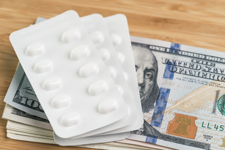 Pharmacy, health care or medical expense concept, white package of pills on pile of US dollar banknotes money, patient have to pay for their better life
